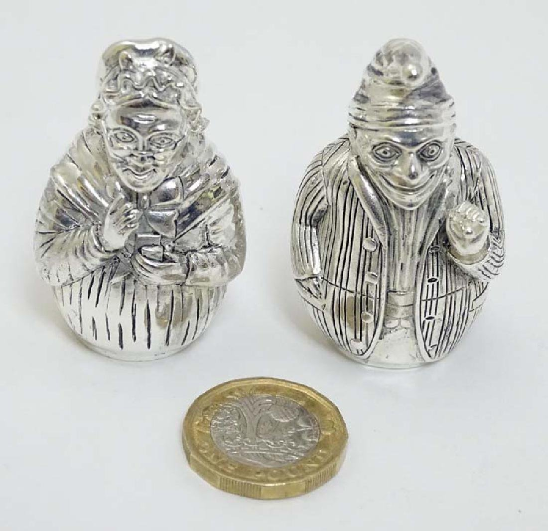 A pair of white metal  novelty pepperettes formed as