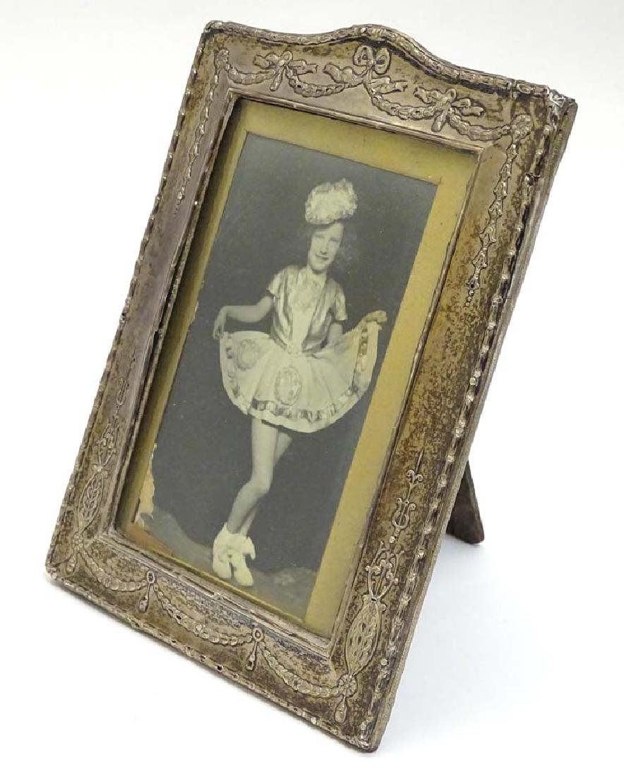 A silver frame with bow harebell and swag decoration.