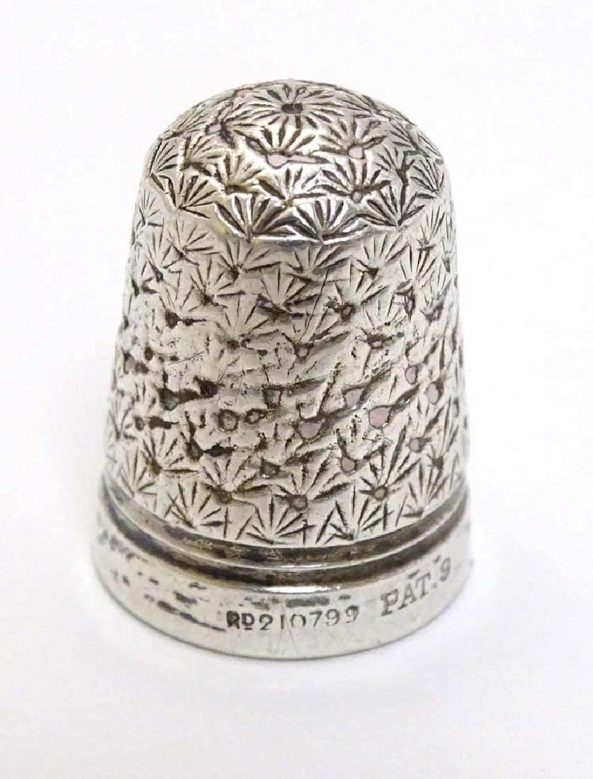 A white metal thimble with reg des. no for c.1893 3/4''