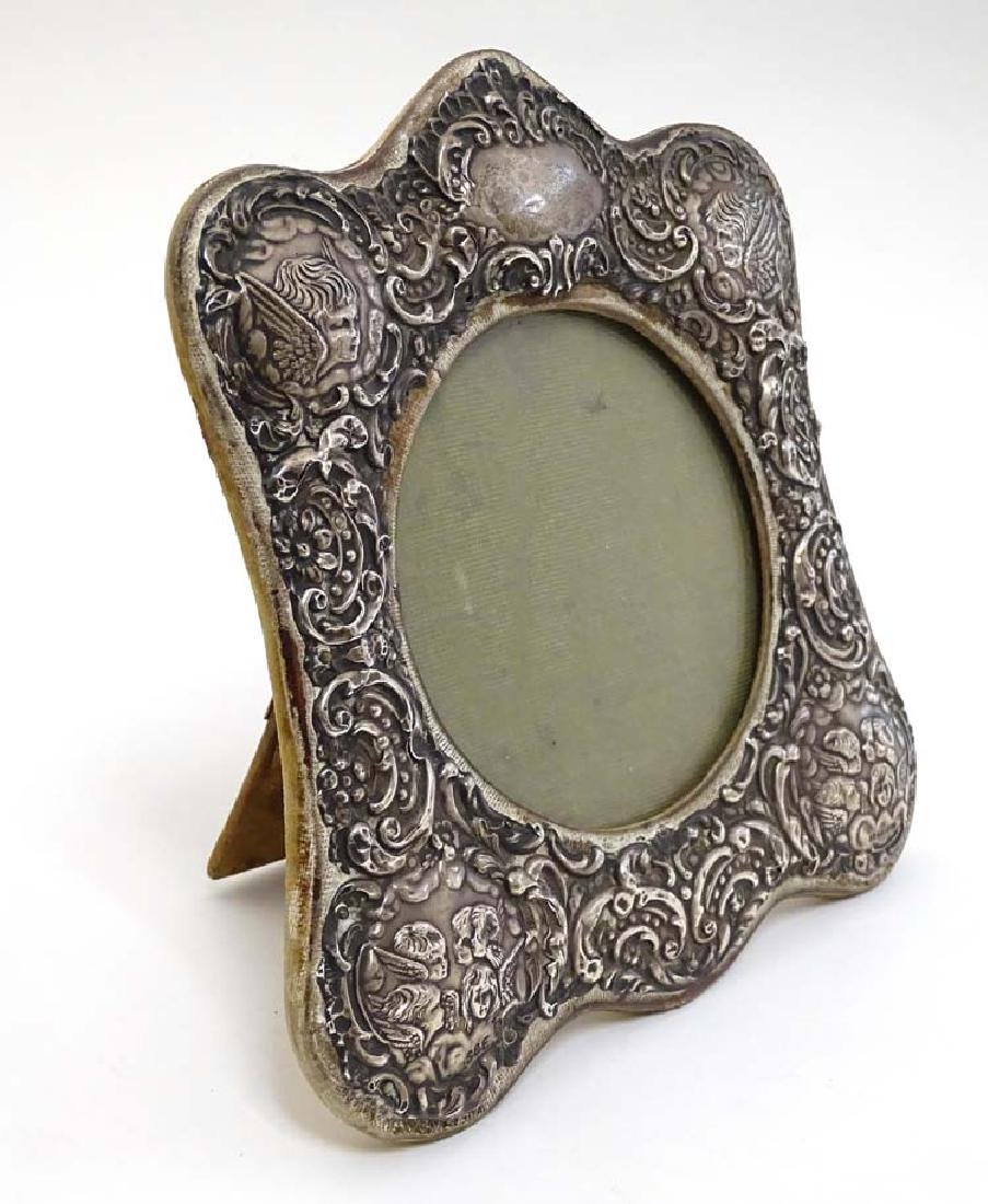 A silver photograph frame with embossed cherub,
