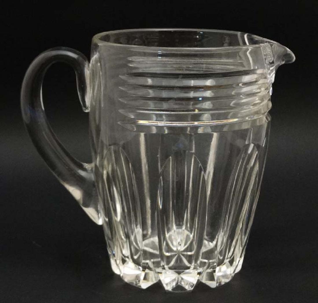 A heavy cut glass jug with loop handle 7'' high