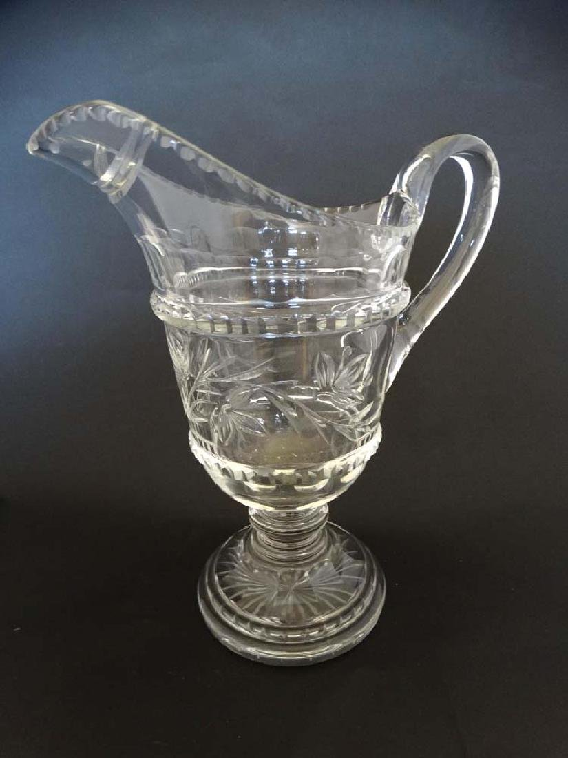 A clear glass / crystal pedestal jug with loop handle
