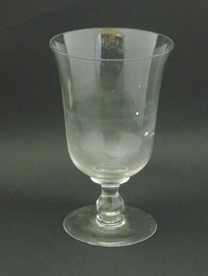 A large clear glass celery vase on pedestal base and