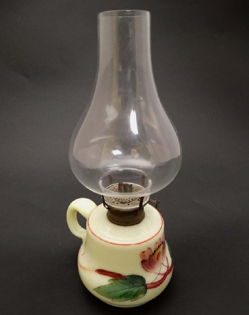 A small glass oil lamp with floral decoration, loop