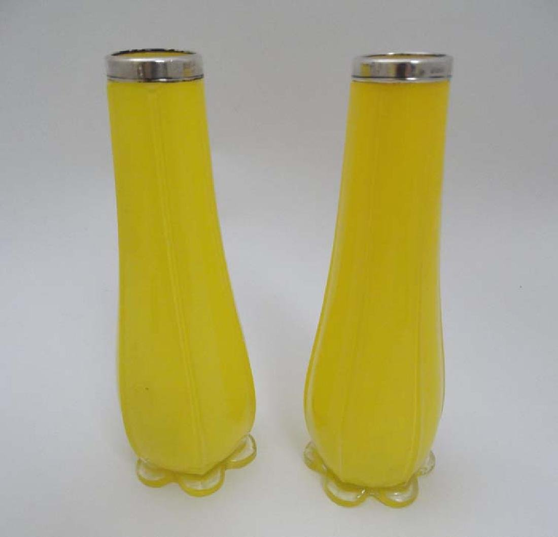 A pair of yellow glass vases with silver collars