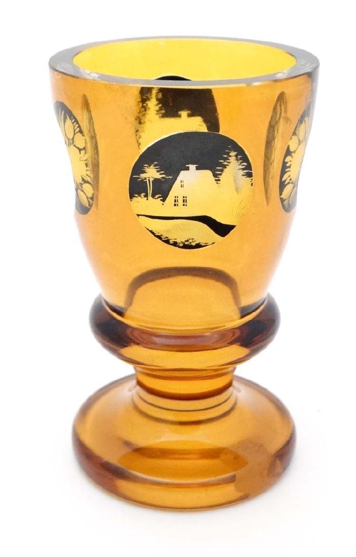 A Bohemian amber glass vase of goblet form with black