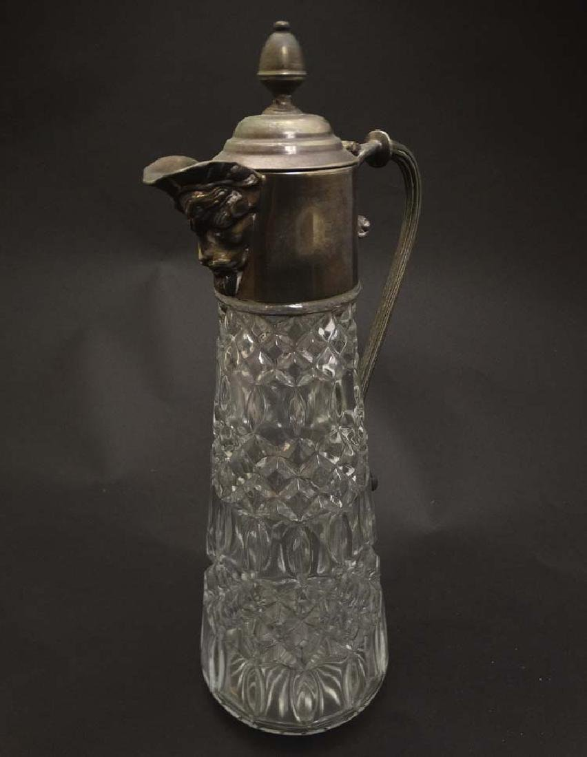 A glass claret jug  with silver plate handle and mounts