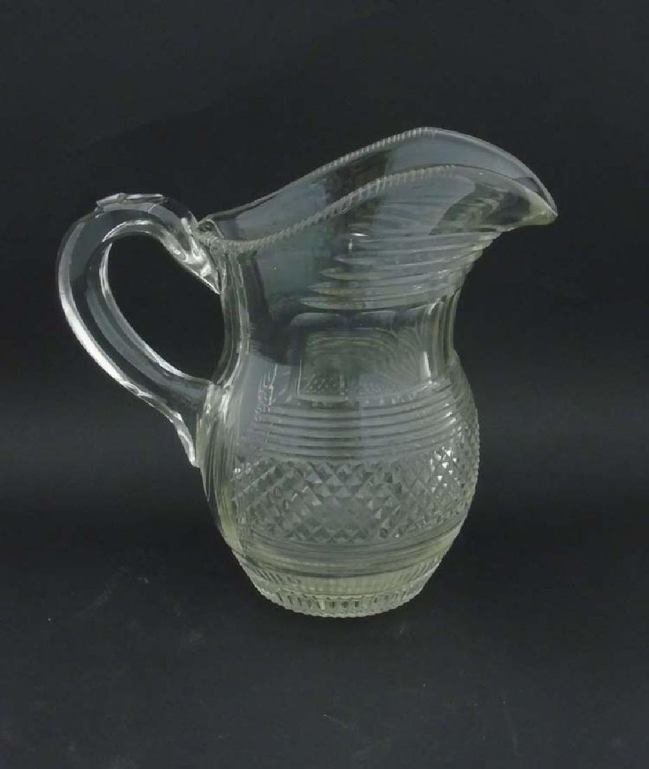 A 19thC clear cut glass crystal jug with loop handle. 8