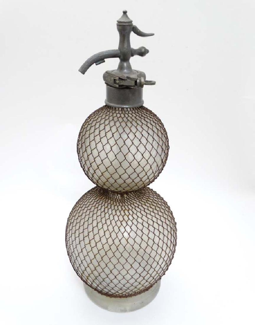 A large glass soda siphon with mesh covering and grip