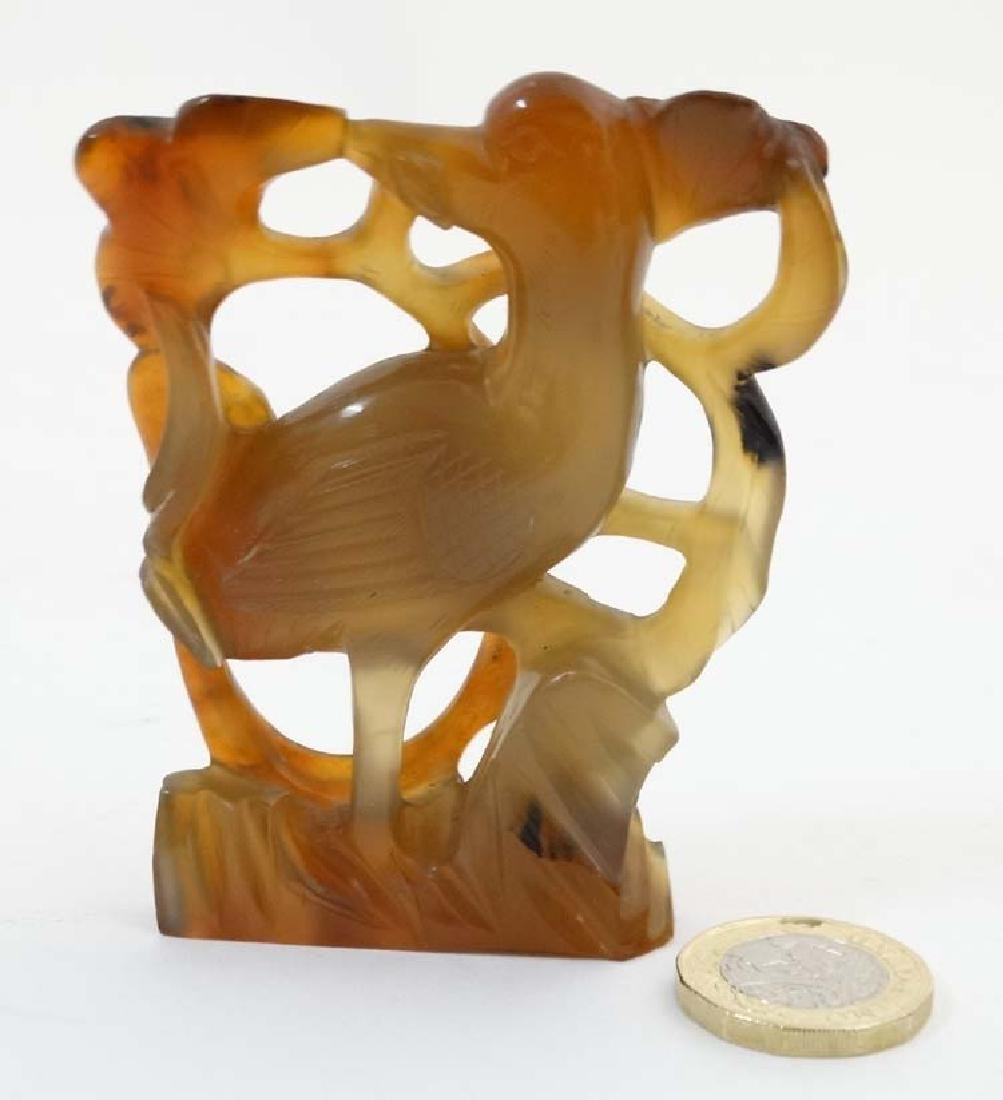 A carved russet jade ornament of a bird amongst