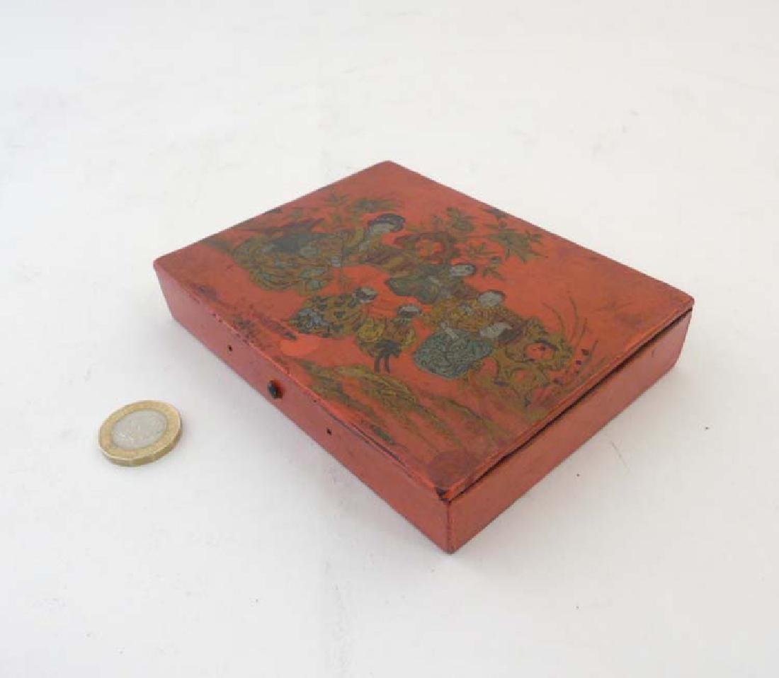 A Japanese lacquered persimmon red seal box depicting a