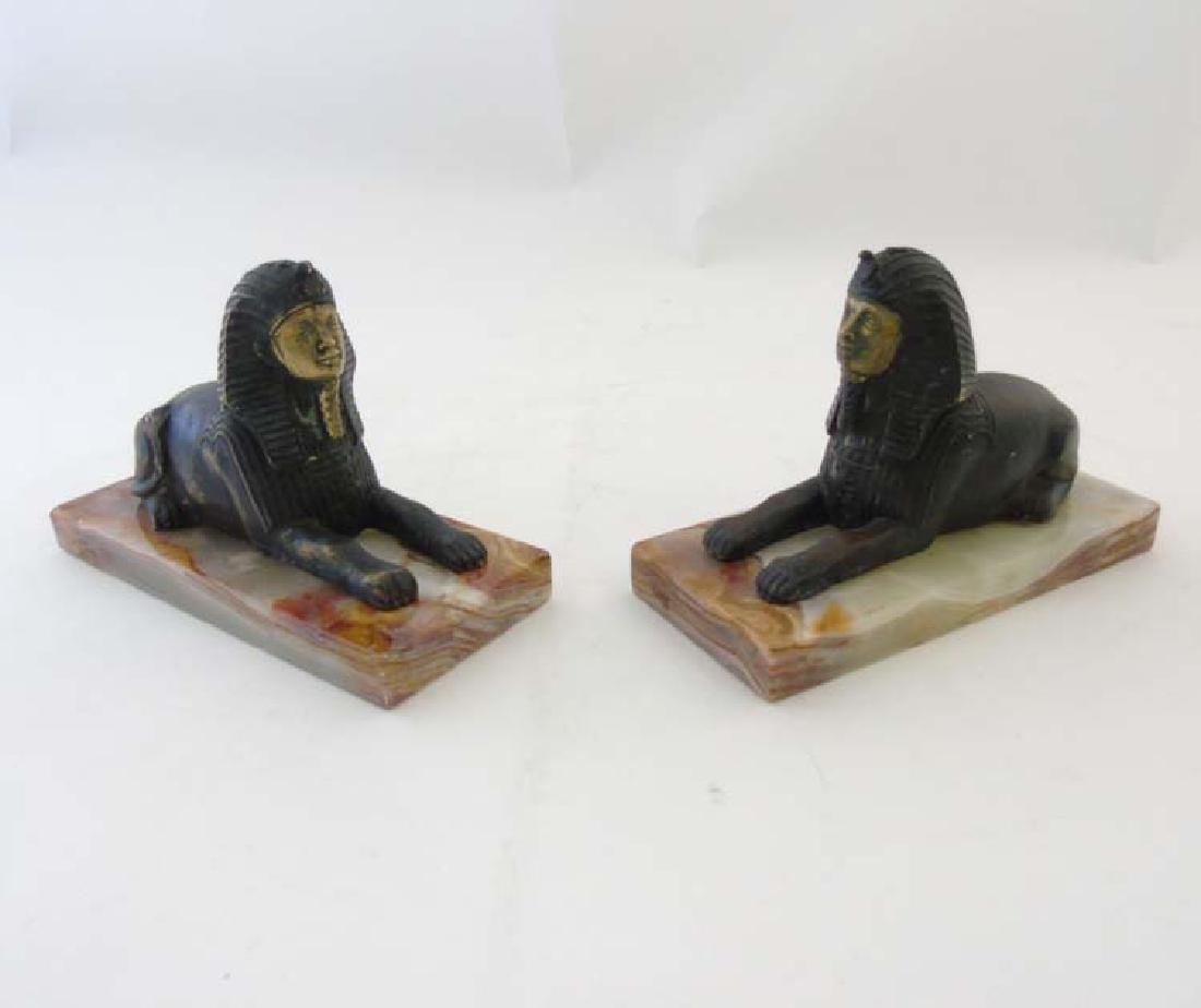 A pair of gilded bronze Egyptian sphinx on onyx bases.