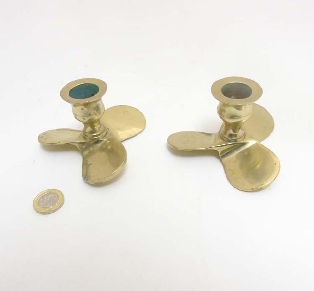 A pair of 20thC cast brass candlesticks formed as