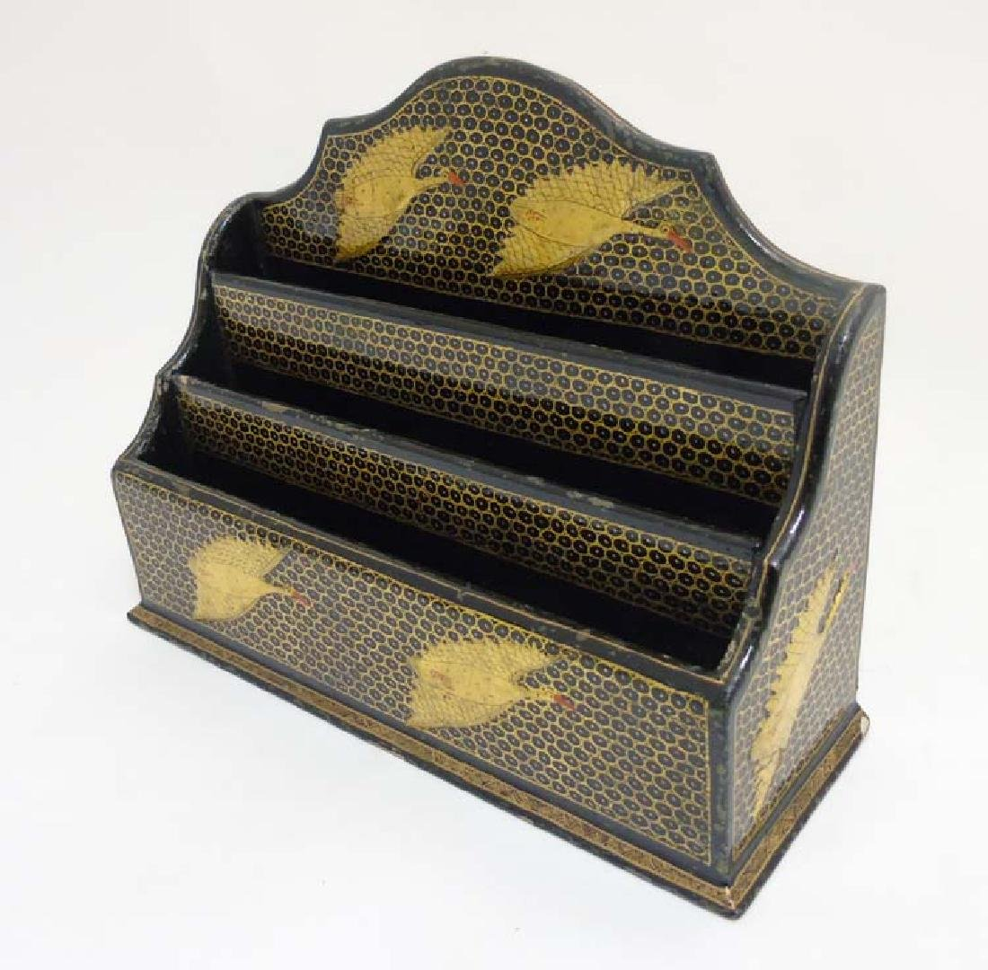 An Indian gilt decorated and black letter rack with