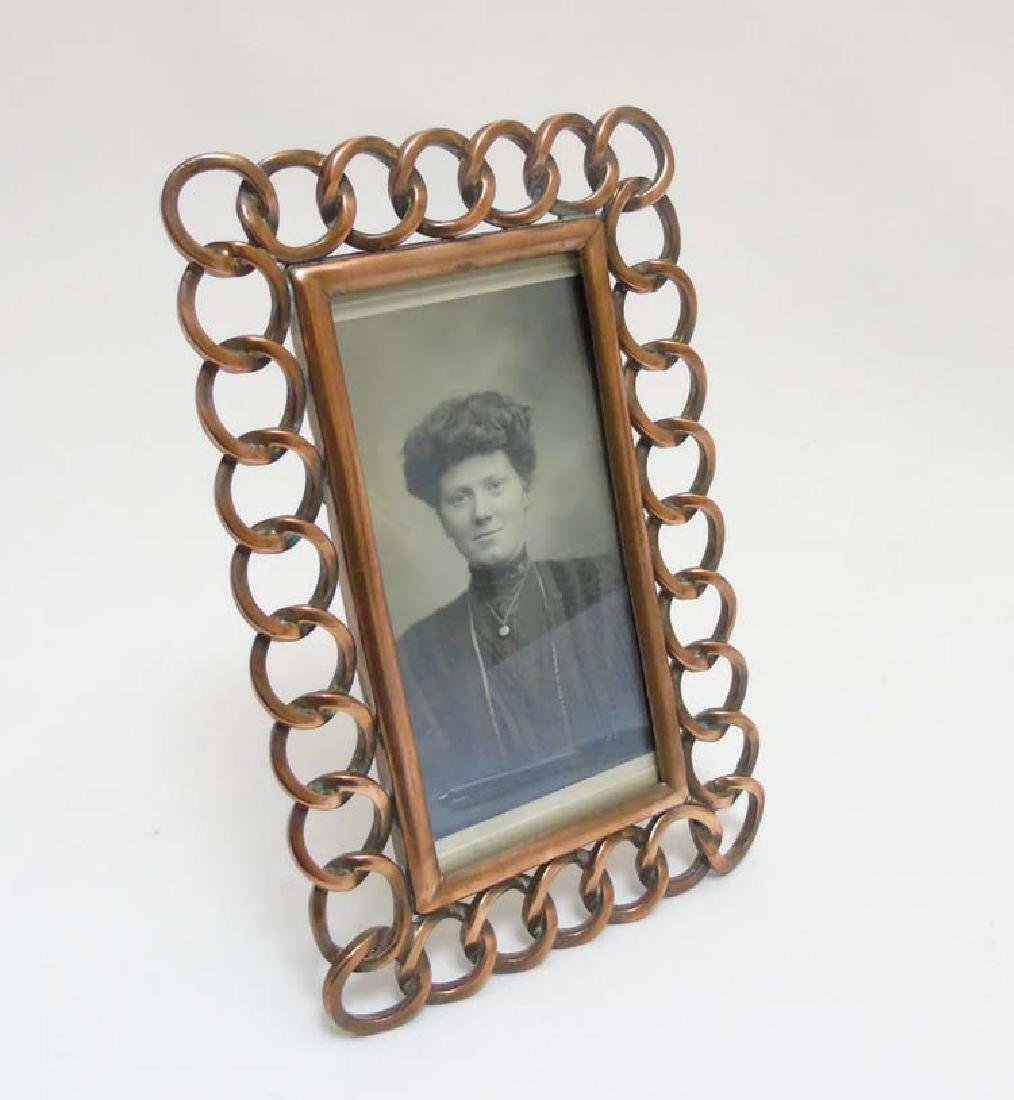 An Edwardian copper photograph frame with curved chain