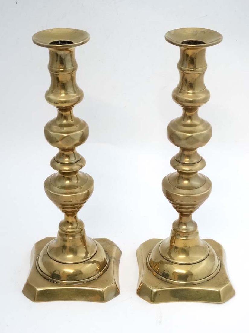A pair of brass candlesticks with plungers. Approx 11