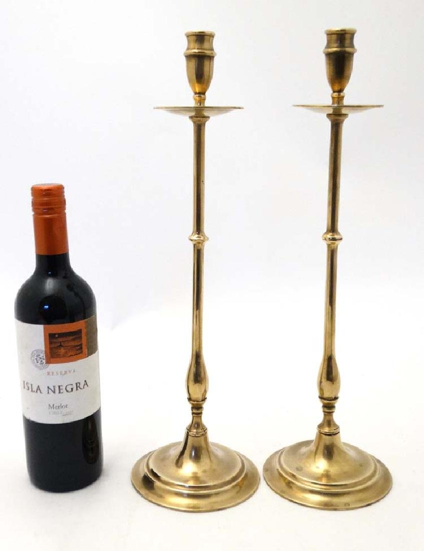 A pair of early 20thC tall brass candlesticks with