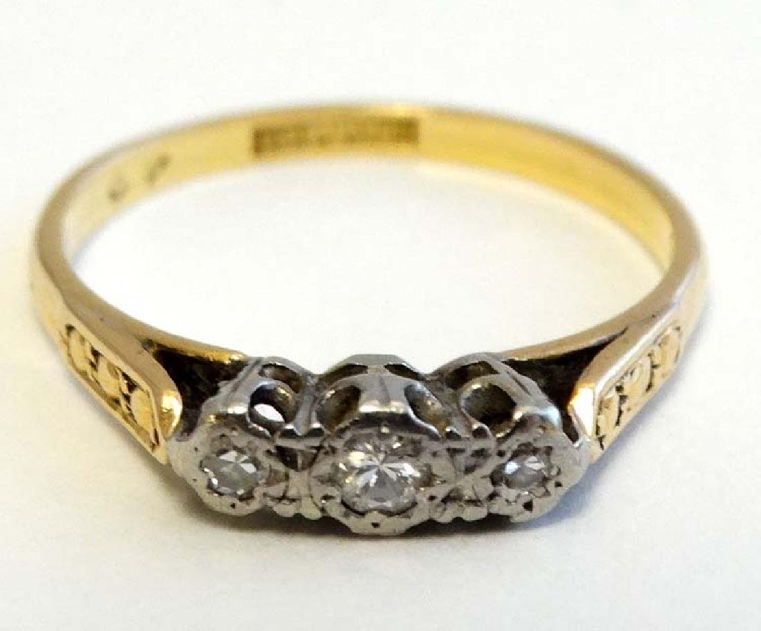 An 18ct gold ring with trio of diamonds to top