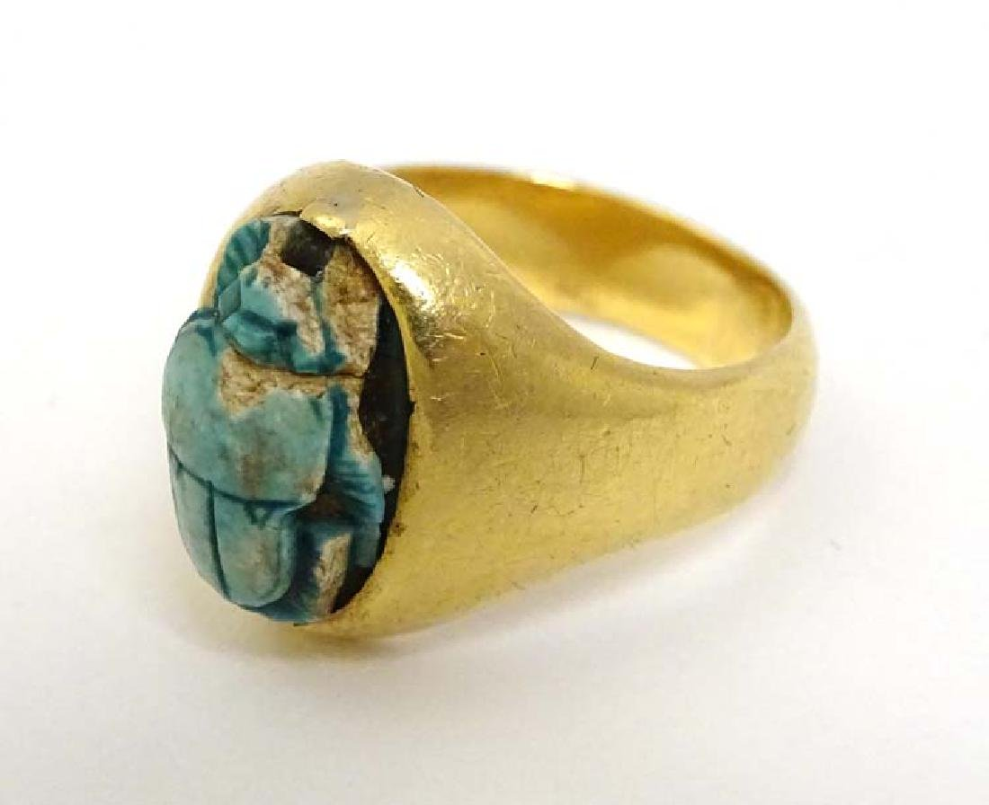 A yellow metal ring set with ceramic cabochon formed as