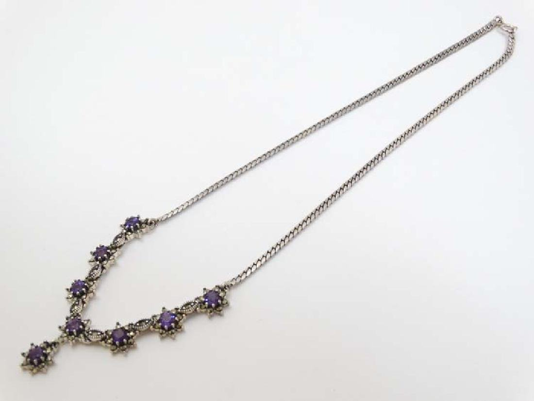 A white metal necklace set with amethysts. Approx 16''