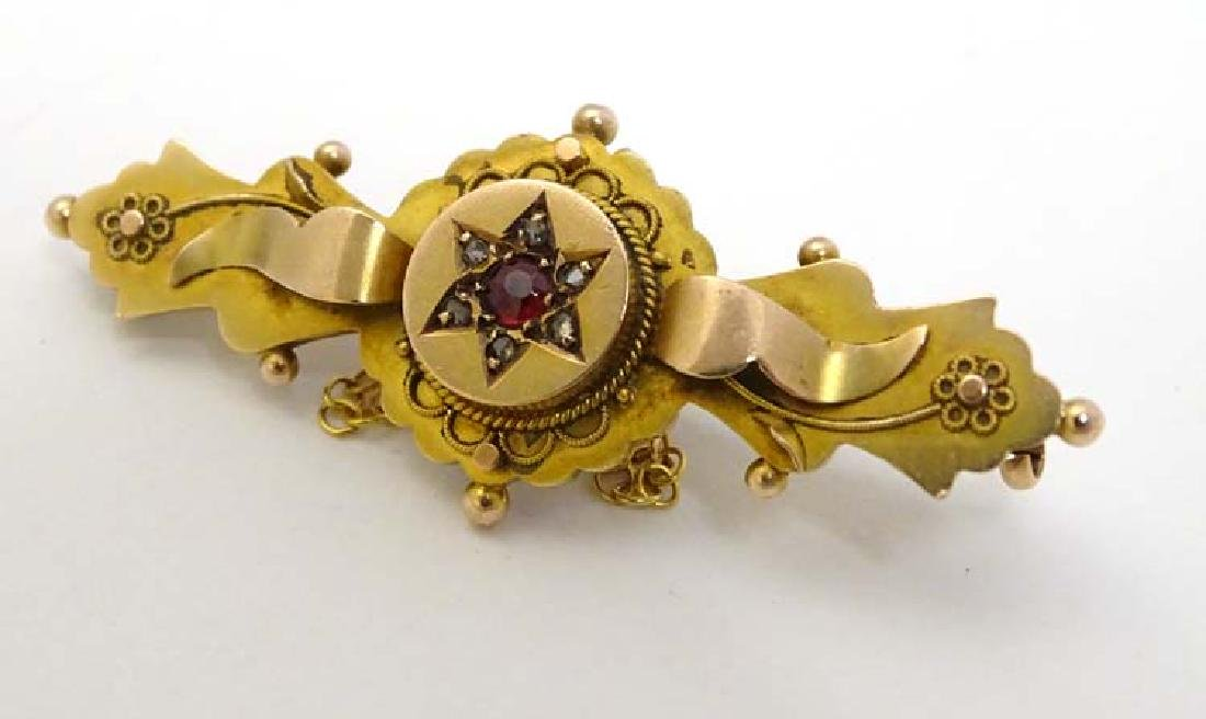 A 9ct gold bar brooch set with red stone and diamonds