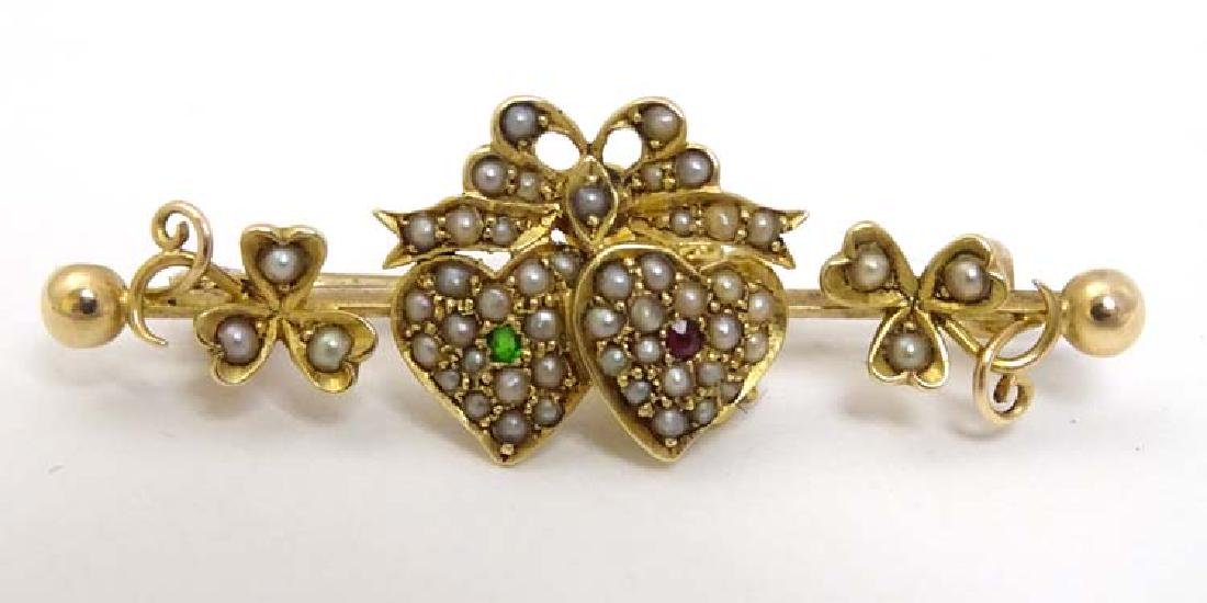 A 9ct gold and gilt bar brooch with bow and heart