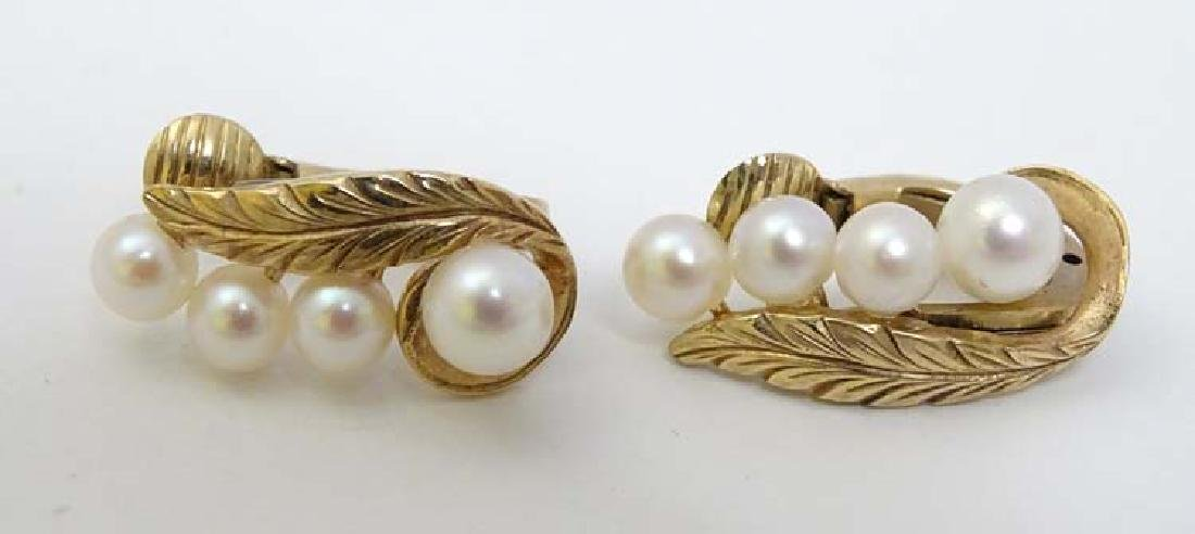 A pair of 9ct gold clip earrings set with 4 graduated