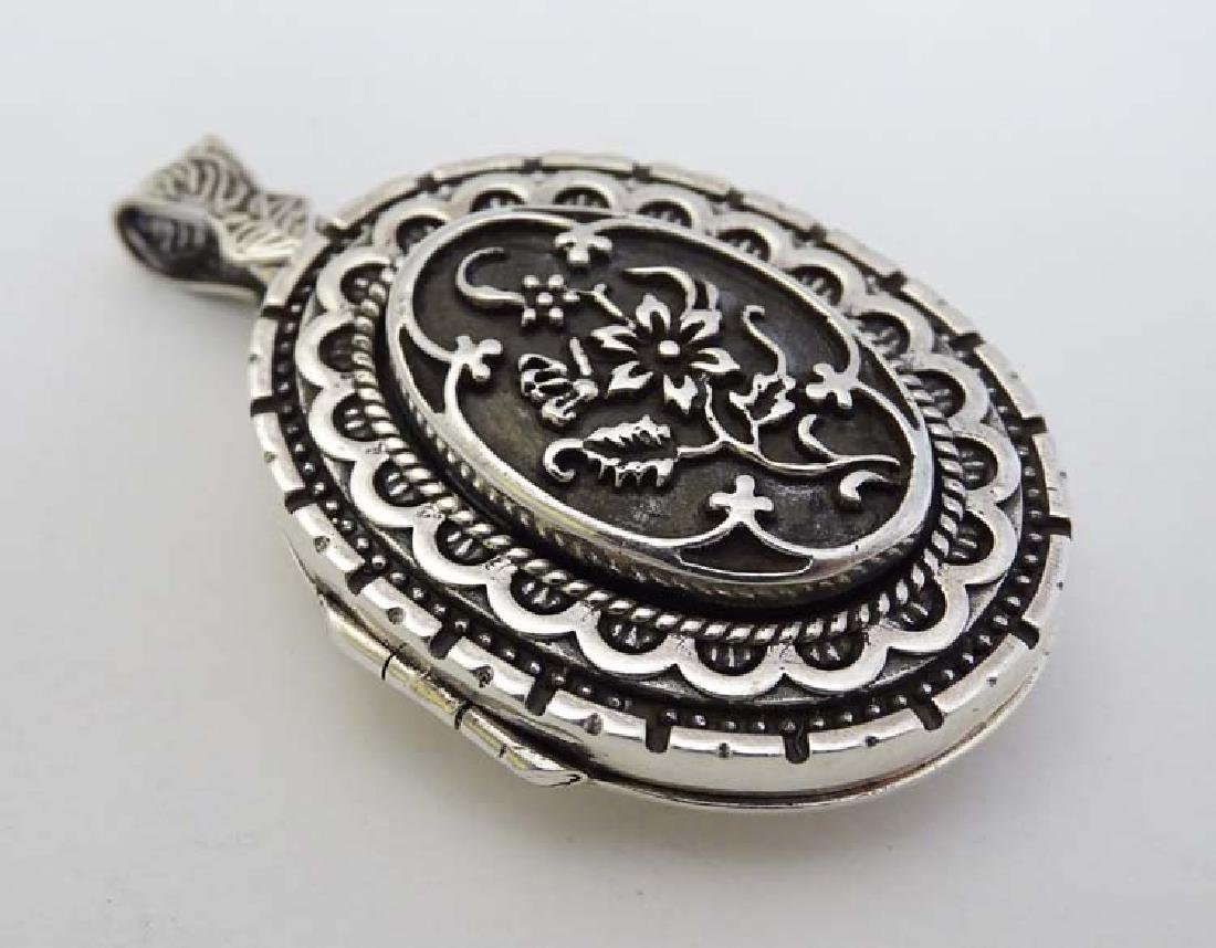 A large silver locket of oval form with floral