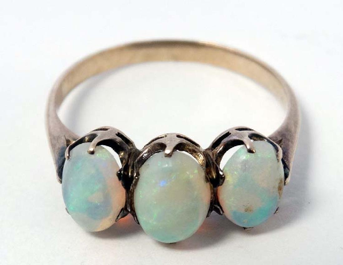 A yellow metal ring set with three graduated opals