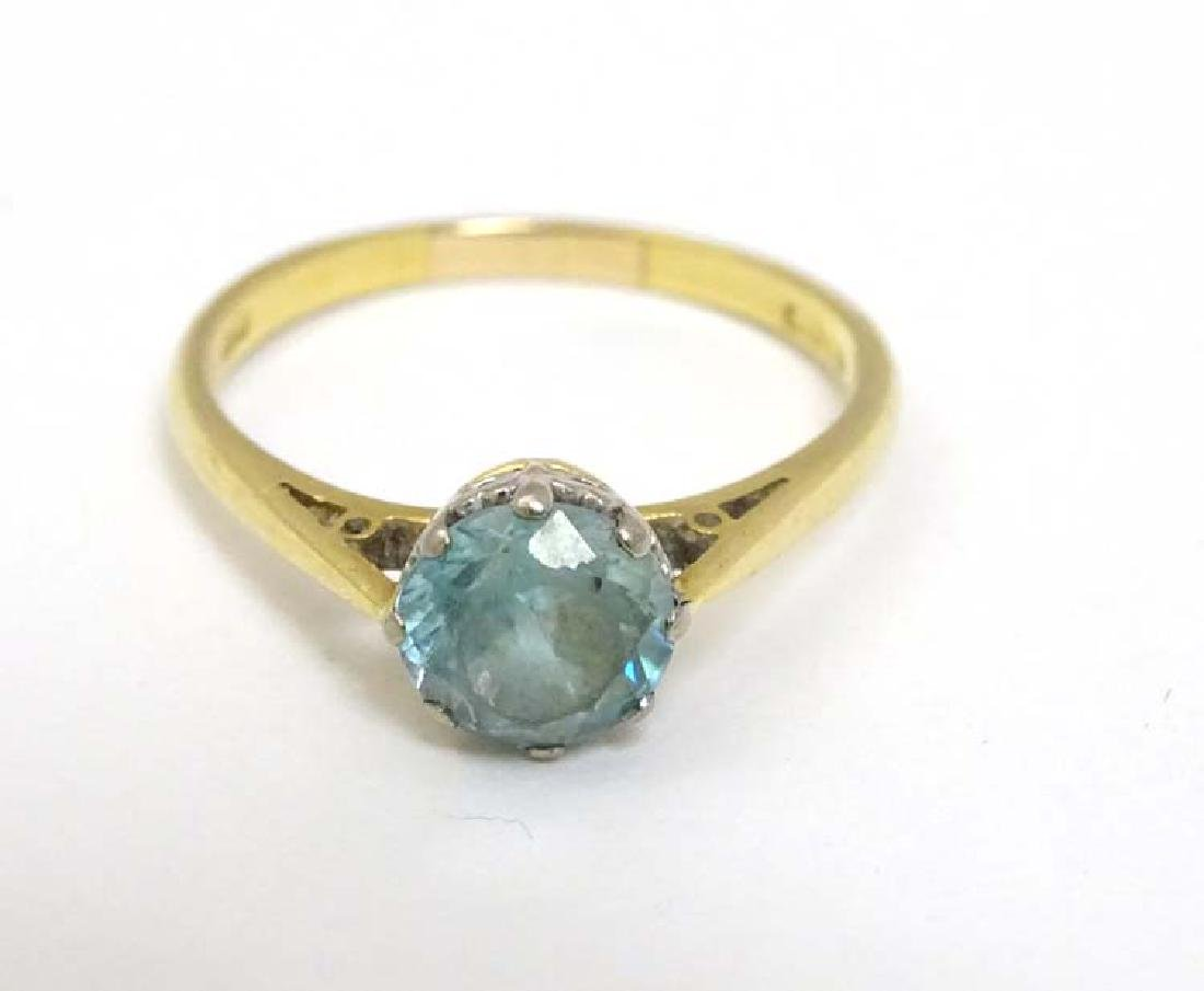 An 18ct gold ring set with aquamarine coloured stone