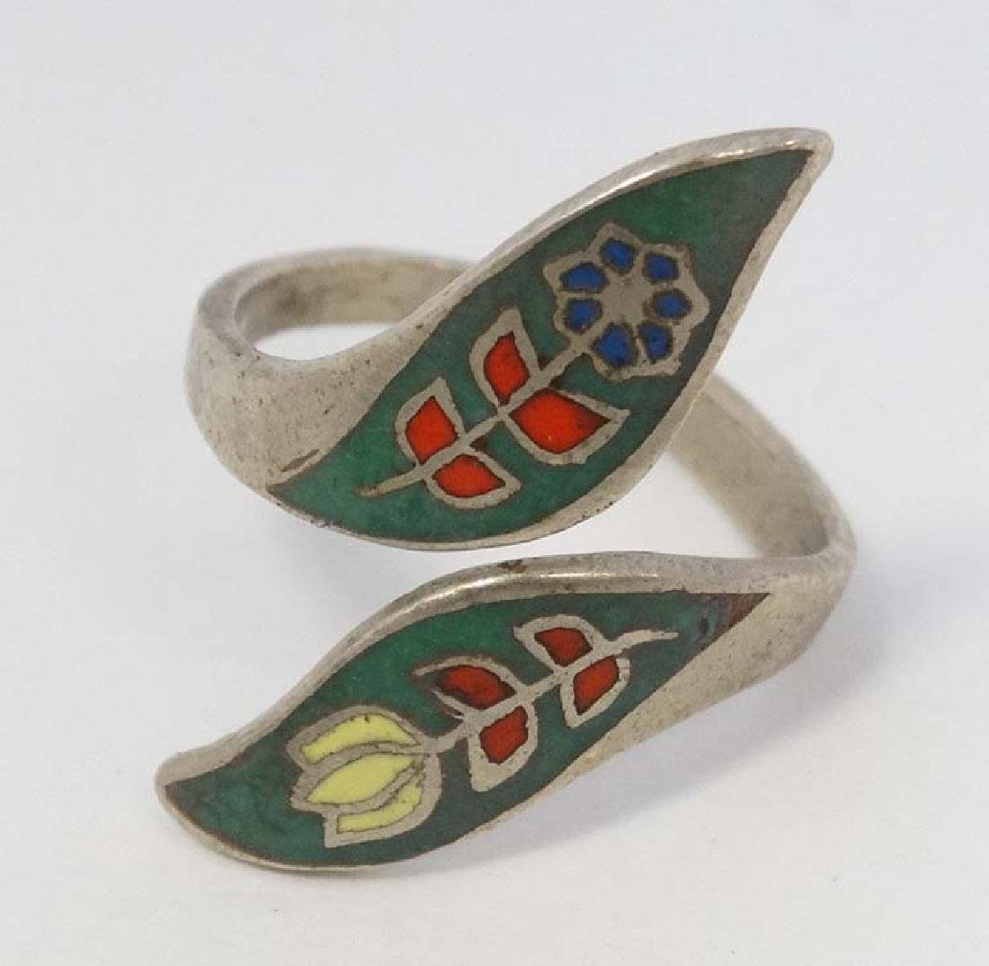 A white metal ring with enamel decoration.