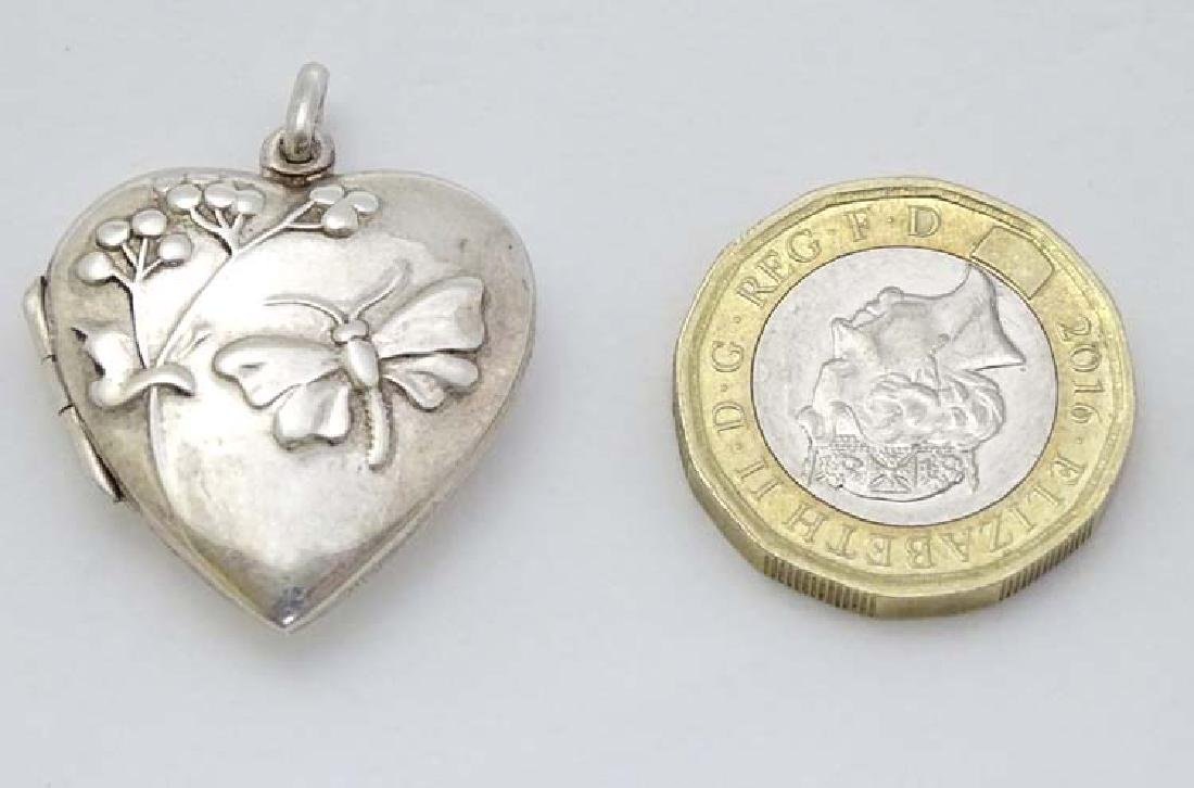 A silver heart shaped locket with foliate and butterfly
