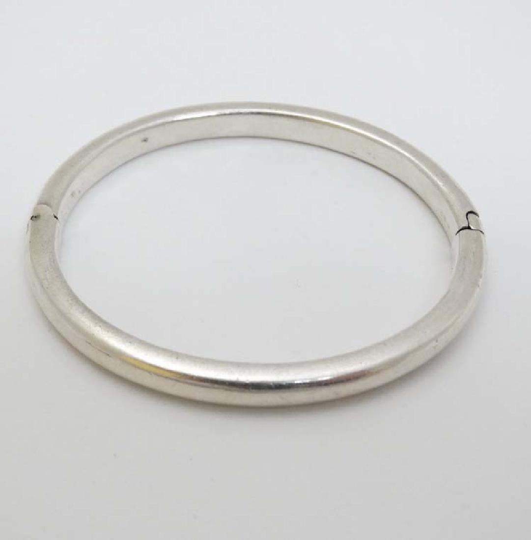 A white metal bracelet of bangle form .