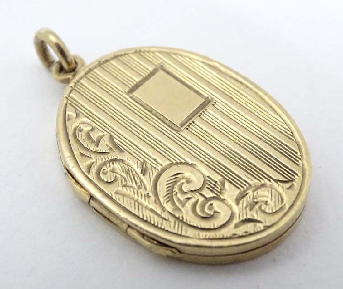 A 9ct gold locket of oval form hanging engraved
