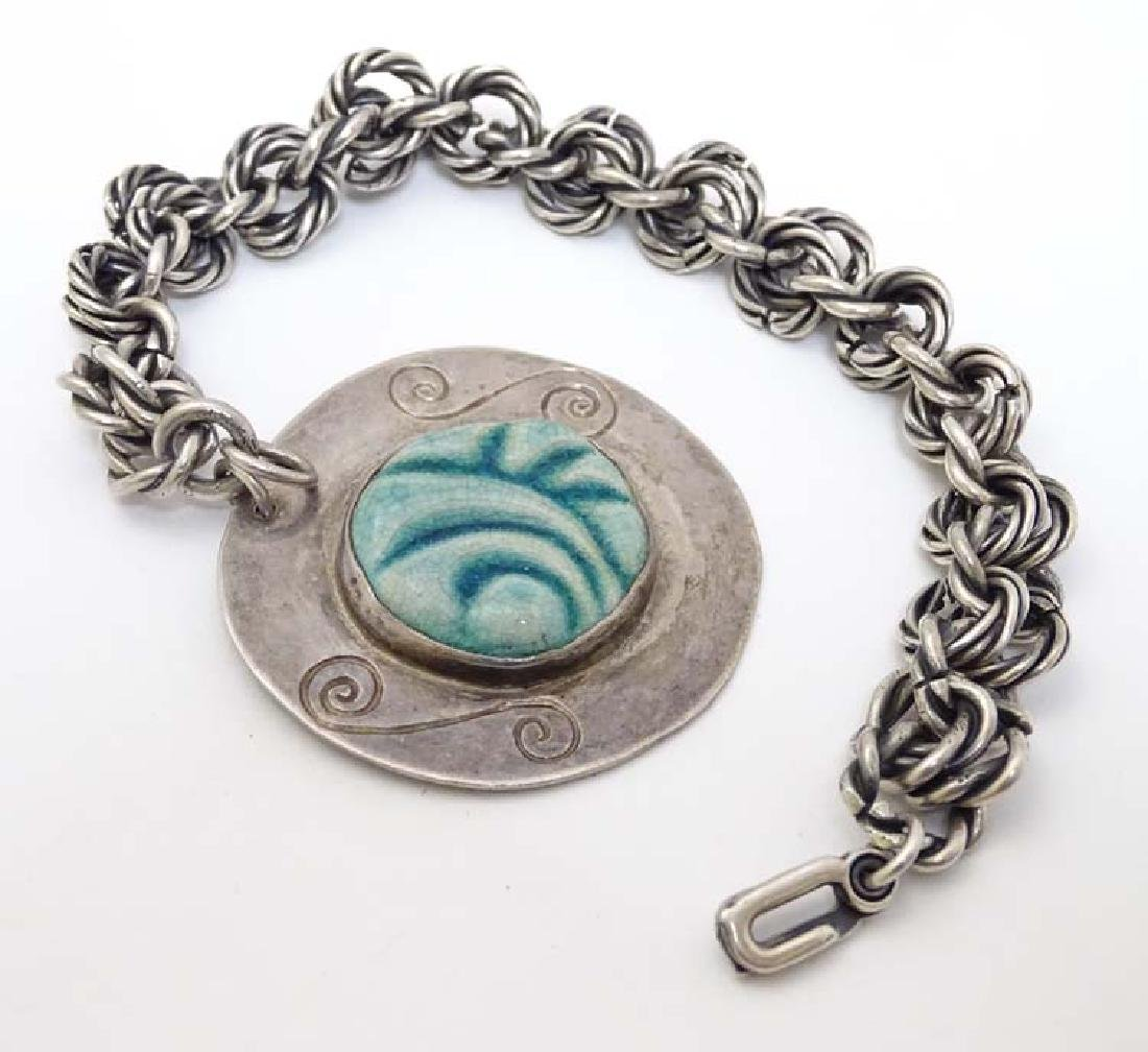 A silver bracelet with large pendant  having central