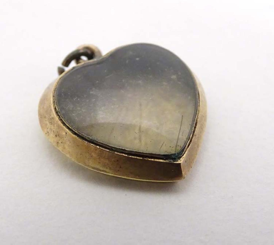 A yellow metal pendant locket of heart form with