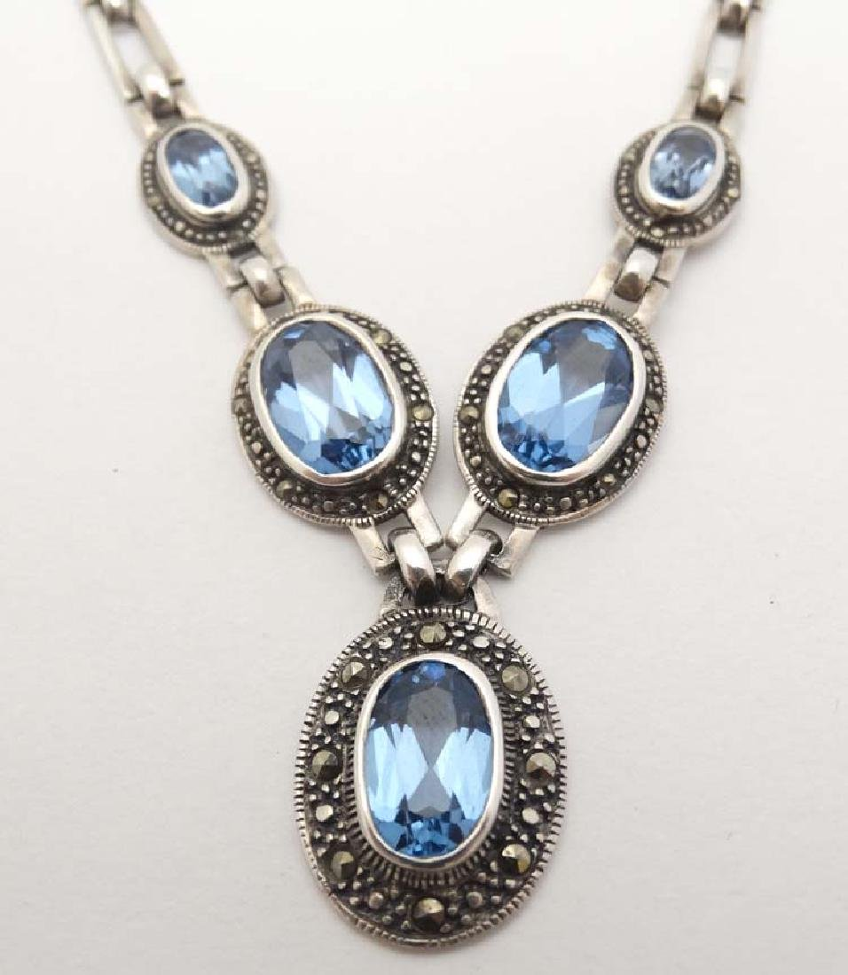 A silver necklace set with 5 oval topaz coloured blue