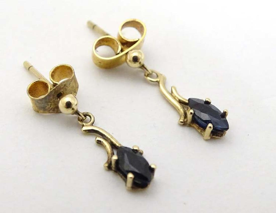 A pair of 9ct gold earrings set with sapphire drops