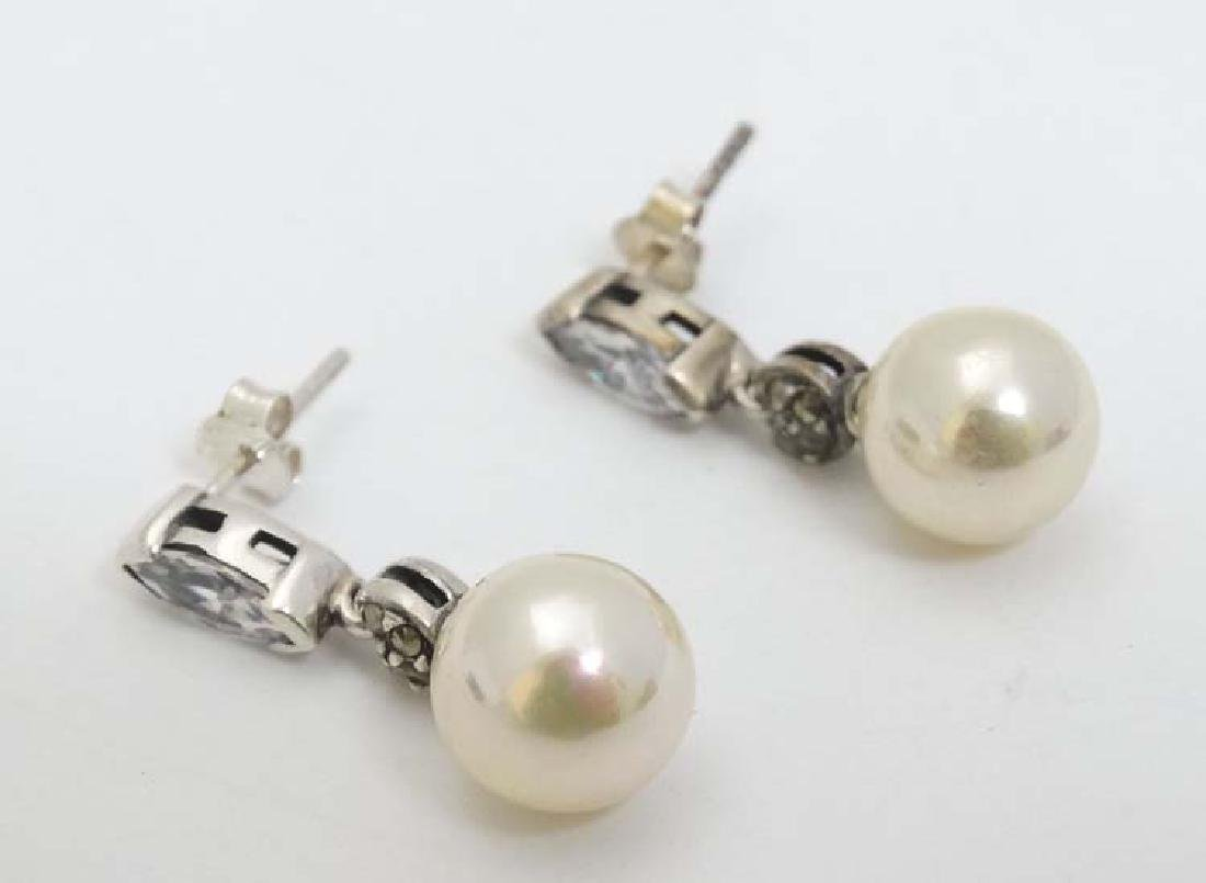 A pair of white metal drop earrings set with white