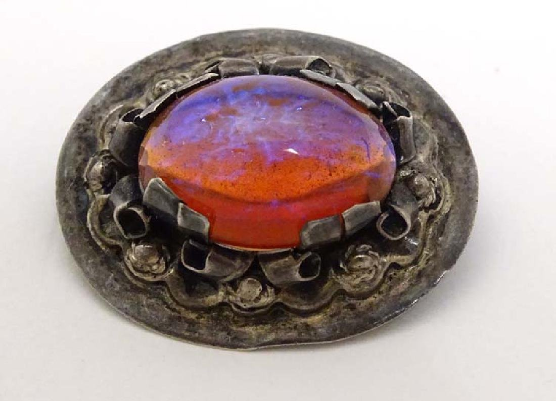 A Mexican silver brooch of oval form with cabochon to
