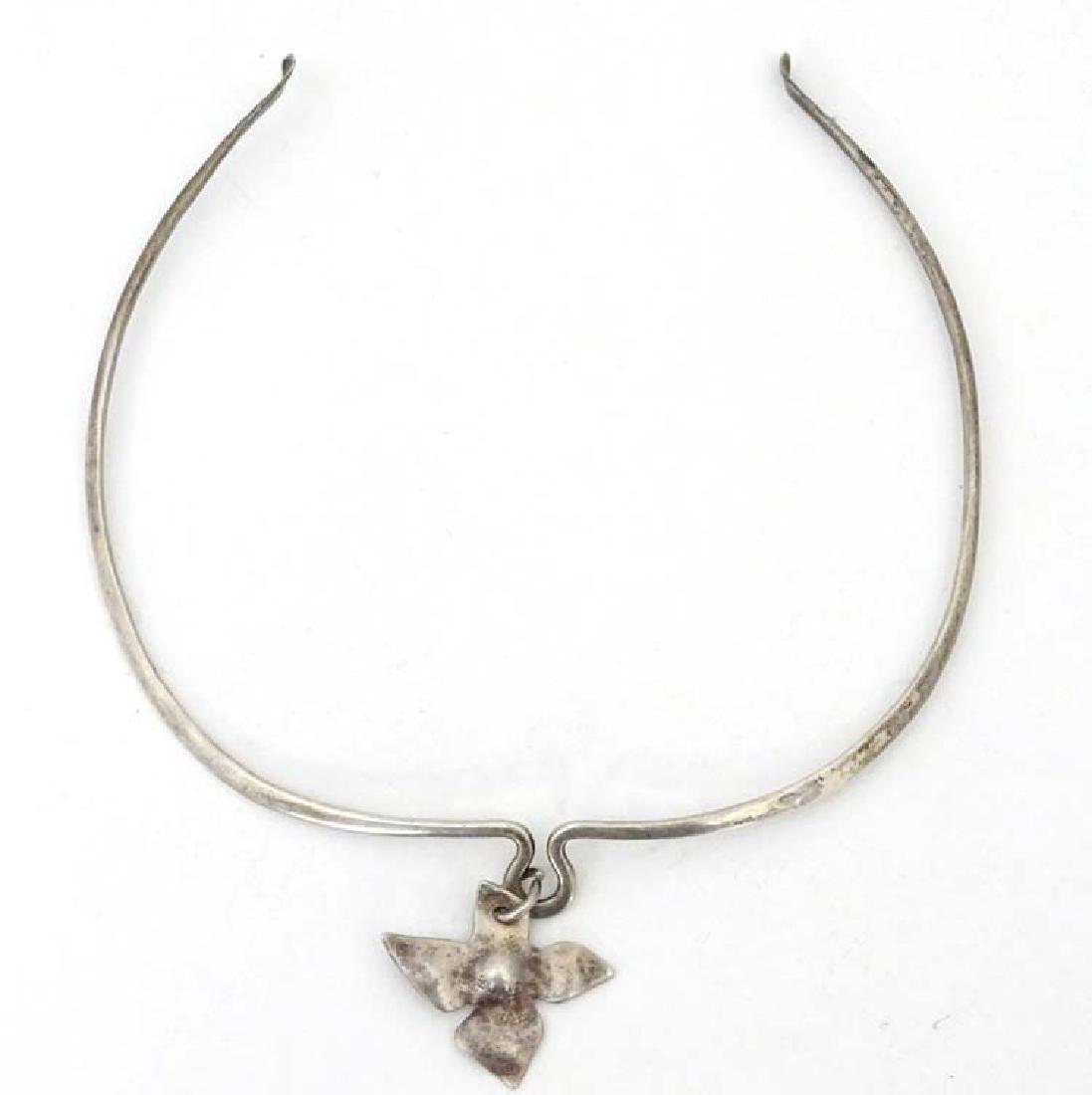 A white metal necklace of choker form with quatraform