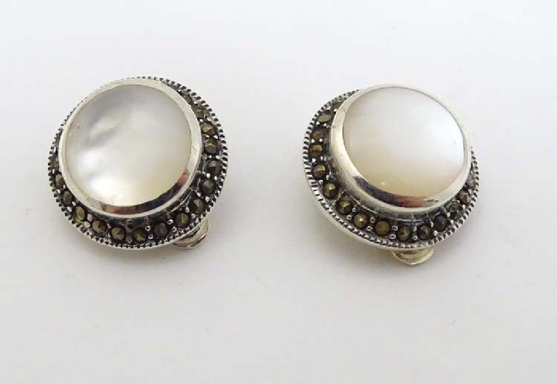 A pair of silver clip earrings set with mother of pearl