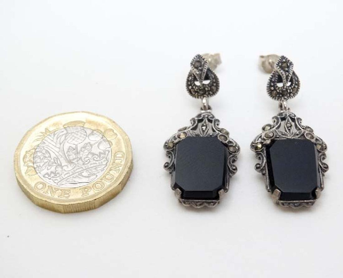 A pair of silver drop earrings set with onyx and
