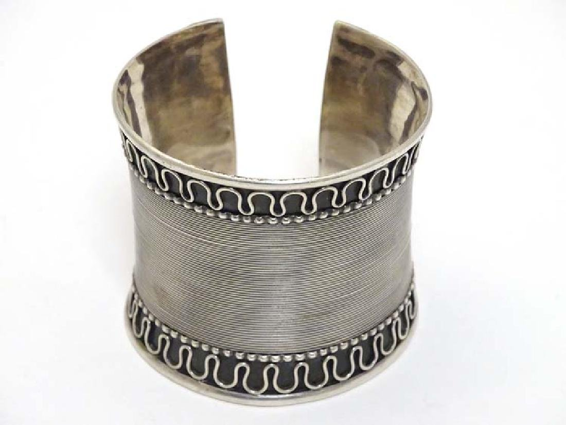A silver bangle / bracelet of cuff form