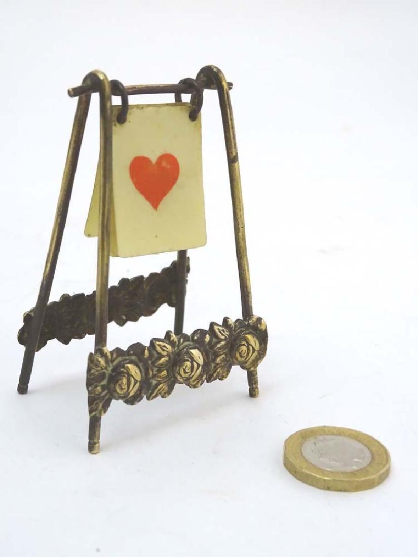 A brass playing card trump marker, 3'' high