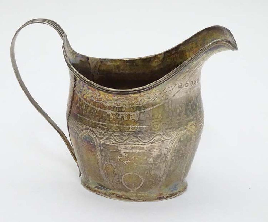 A Geo IIl silver cream jug with engraved decoration and