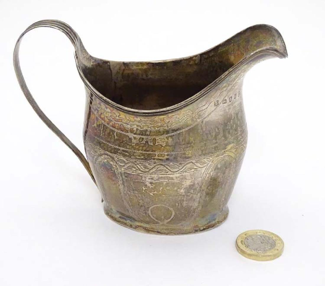 A Geo IIl silver cream jug with engraved decoration and - 3