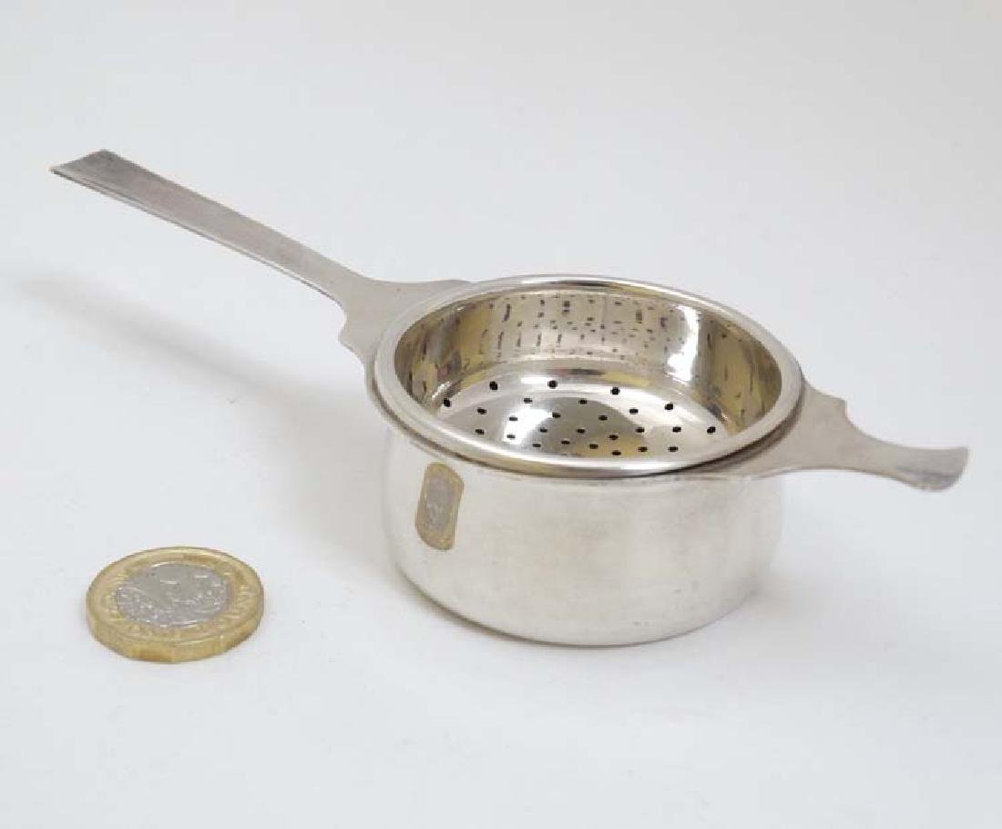 A silver plate tea strainer with stand. 6'' long - 2