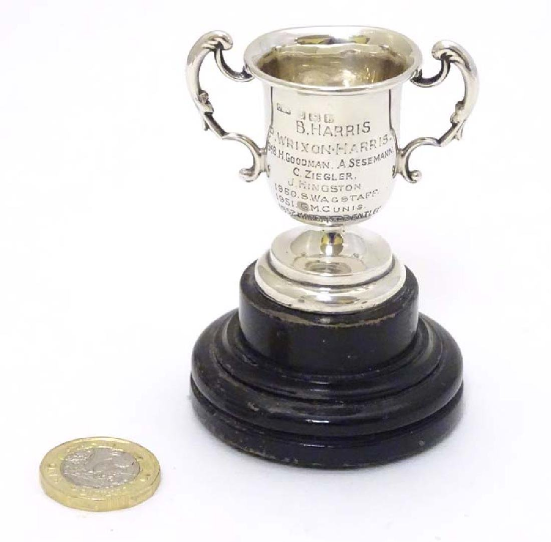 A miniature twin handled trophy cup mounted on a turned