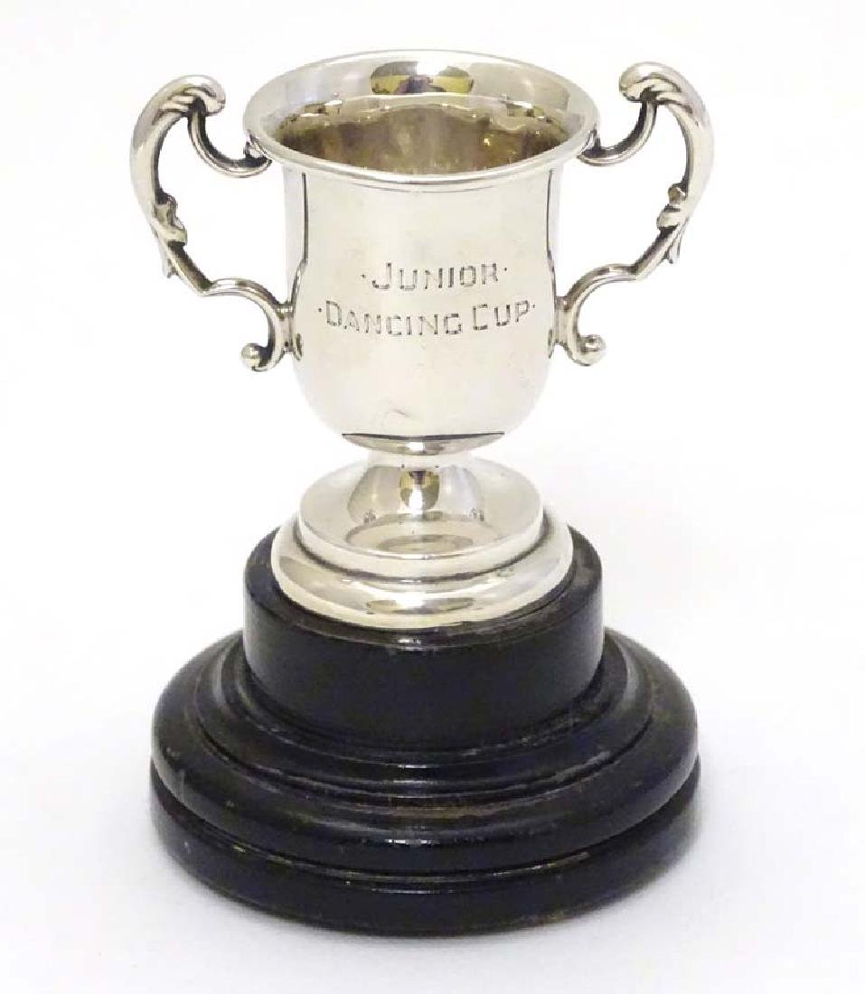 A miniature twin handled trophy cup mounted on a turned - 3